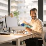 A man holding a book at a computer
