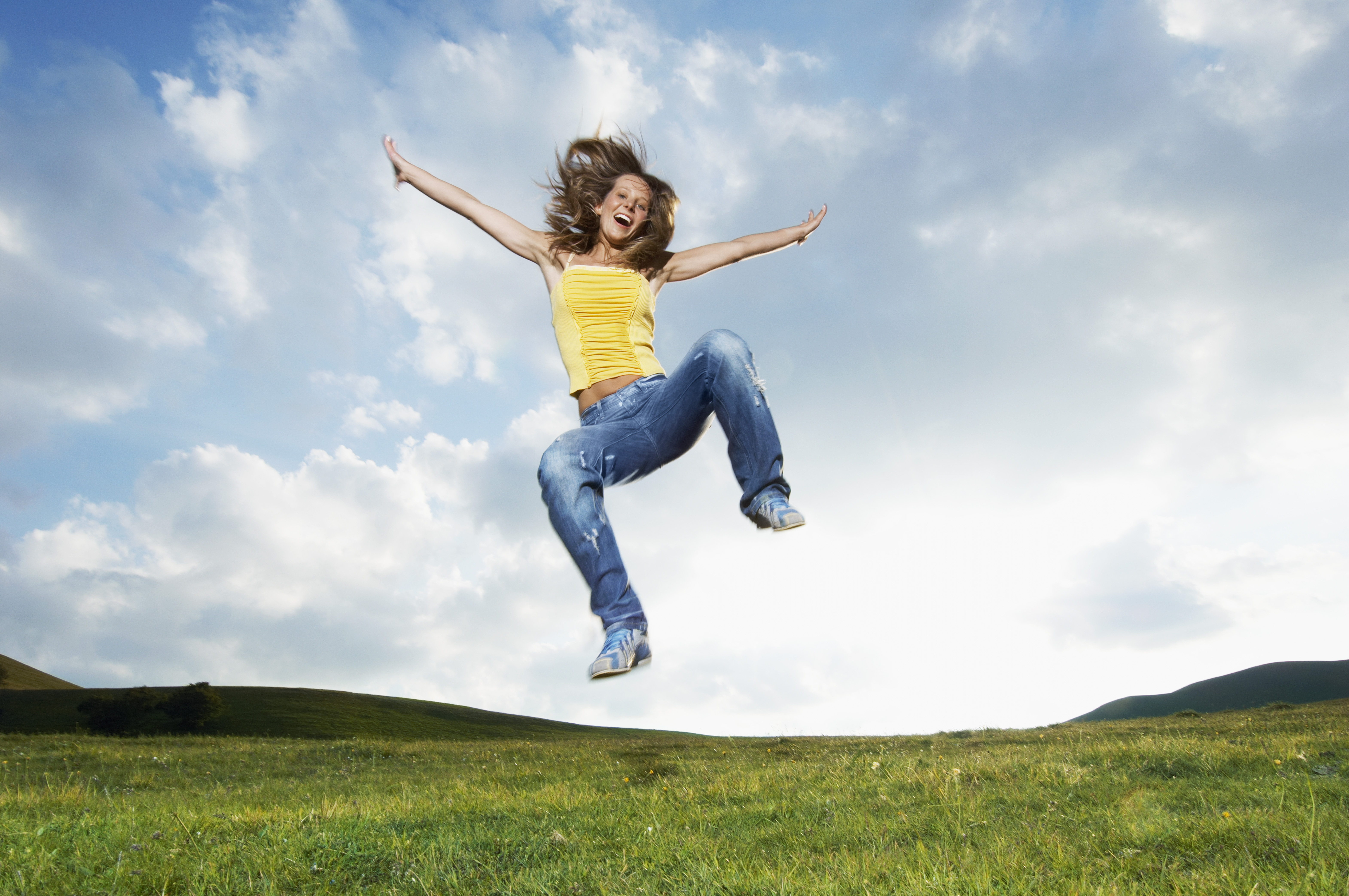 Woman jumping for joy in mountain meadow, front view
